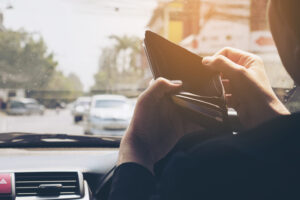 Man look at his empty wallet while driving car, dangerous behavior